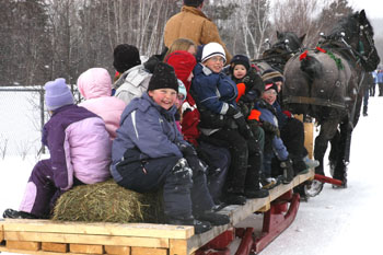 Kids catching a ride on the horse-drawn sleigh